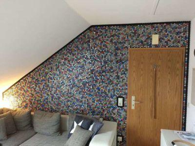 Mur recouvert de capsules de bouteilles en couronne